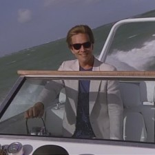 A picture of Sonny Crockett driving a boat. Ray-Ban Wayfarers, an Armani jacket, a plain black T-shirt, and a Wellcraft Scarab 38 KV was all that Sonny